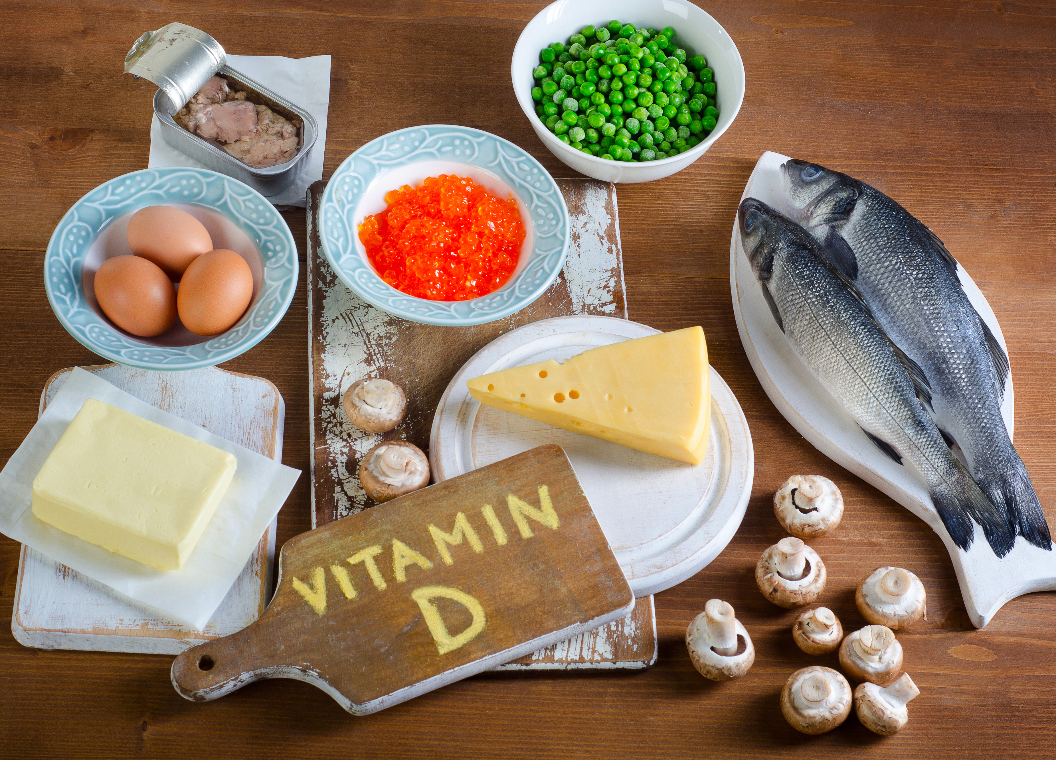 Foods highest in vitamin D on wooden background.
