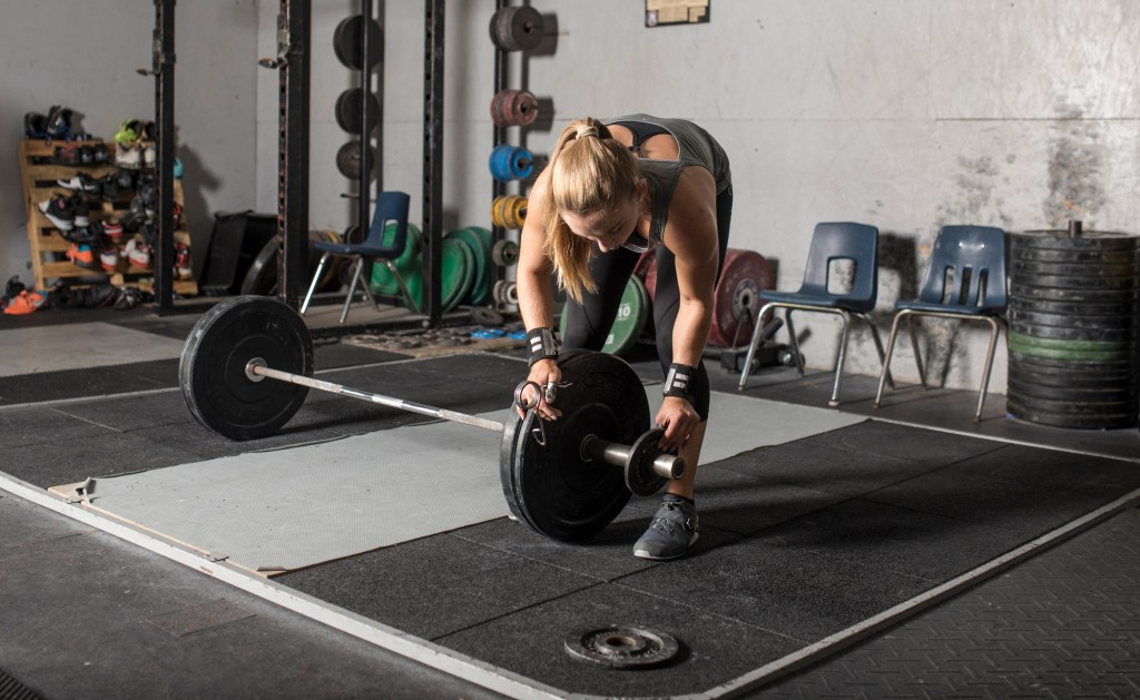 Woman adding weight to improve fitness performance.